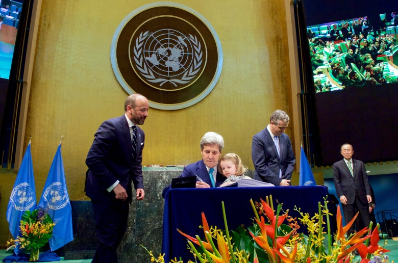 Secretary_Kerry_Holds_Granddaughter_Dobbs-Higginson_on_Lap_While_Signing_COP21_Climate_Change_Agreement_at_UN_General_Assembly_Hall_in_New_York_(26512345421)